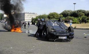 Une voiture renversée alors que des taxis bloquent le passage Porte Maillot à Paris, le 25 juin 2015