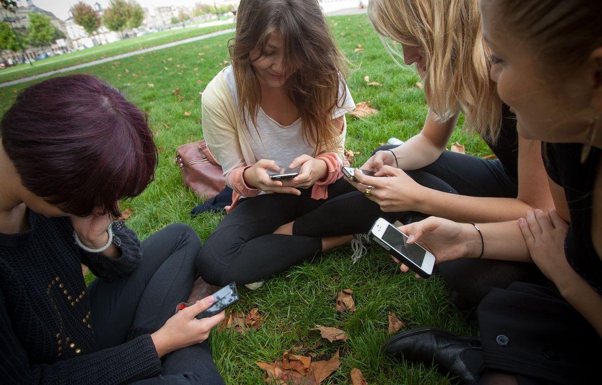 Des adolescentes utilisent leurs smartphones dans la ville de Bordeaux, en 2013. Illustration –  POUZET/SIPA