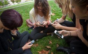 Des adolescentes utilisent leurs smartphones dans la ville de Bordeaux, en 2013. Illustration