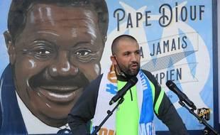 Omar Keddadouche devant la fresque en hommage à Pape Diouf lors de son inauguration.