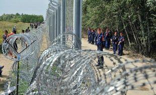 Migrants et réfugiés le 15 septembre 2015 d'un côté de la clôture barbelée  près de Horgos en Serbie,   gardée de l'autre côté par la police hongroise