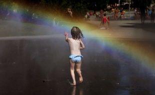 Une petite fille se précipite vers un arc-en-ciel devant une fontaine dans un parc, à Madrid, le 21 juin (illustration)