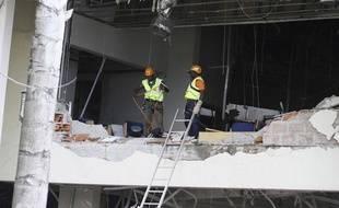 Des secouristes travaillent dans le bâtiment éventré de l'ONU quelques heures après l'attaque à la voiture piégée qui a tué au moins 18 personnes, vendredi 26 août à Abuja (Nigéria)