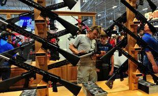 Un hommeet son fils observent un fusil d'assaut lors du congrès annuel de la la National Rifle Association (NRA), le 11 avril 2015 à Nashville, dans le Tennessee
