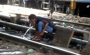 Un Indien se rafraîchit près d'une voie ferrée à New Delhi le 27 juin 2014