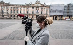 Une journaliste Place du Capitole alors que la France passe en confinement le 17 mars a midi pour contenir l'épidémie liée au Coronavirus.
