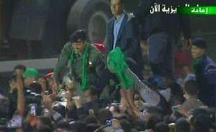L'un des fils de Mouammar Kadhafi, Khamis (à gauche), salue la foule le 29 mars 2011 à Tripoli (Libye).