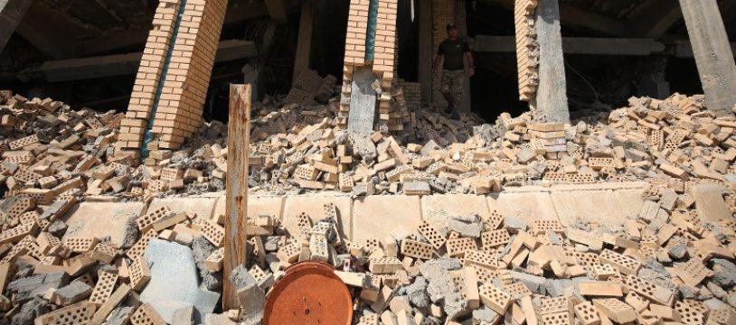 Un soldat irakien devant la tombe en ruines de Saddam Hussein.