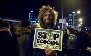 Un protestataire, pendant la COP25 à Madrid, tient une pancarte dans la main mentionnant «   Stop à l'écocide, changez la loi »
