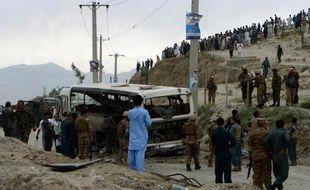Inspection d'un bus ravagé par un attentat suicide à Kaboul, le 26 mai 2014