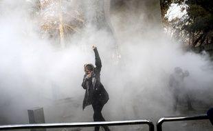 Un étudiant participe à une manifestation à l'université de Téhéran alors qu'une grenade fumigène est lancée par la police iranienne anti-émeute, samedi à Téhéran, en Iran. 30 décembre 2017. (AP Photo).