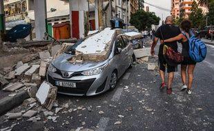 Une femme aide un homme à se rendre à l'hôpital St Georges de Beyrouth avec la violente explosion qui a balayé la ville libanaise le 4 août 2020.