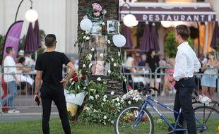 """Des passants regardent un arbre fleuri sur la """"Promenade des Anglais"""" à Nice pour les commémorations en hommage aux victimes de l'attentat du 14 juillet 2016."""