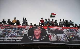 Des manifestants soudanais scandent des slogans en brandissant des drapeaux nationaux soudanais lors d'une manifestation devant le complexe militaire de Khartoum, dans la capitale, le 20 avril 2019.