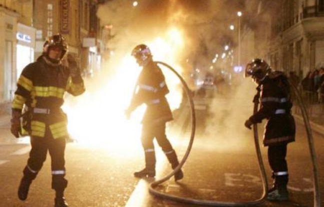 Des pompiers éteignent une poubelle incendiée à Toulouse.