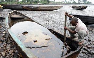 Un habitant de la communauté de Bodo, au sud du Nigeria, tente de séparer avec un bâton le pétrole de l'eau, le 11 août 2011 après une pollution provoquée par la compagnie Shell dans le Delta du Niger