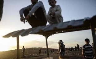 Des Kurdes observent les combats entre jihadistes de l'EI et des combattants kurdes, le 28 septembre 2014 à la frontière avec la Syrie