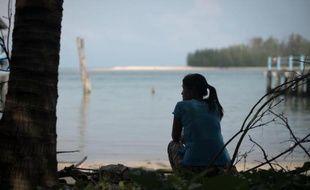 Mi Htay, une Birmane immigrée en Thaïlande qui a perdu trois enfants lors du tsunami, est assise sur une plage près de sa maison à Ban Nam Khem, le 3 décembre 2014
