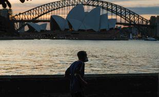 Un adepte de la course à pied passe devant le Sydney Opera House, le 6 août.