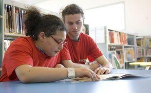 Une jeune fille prend un cours de soutien avec un étudiant bénévole de l'Afev.