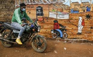 Un homme portant un masque devant une peinture sur les dangers du coronavirus, à Nairobi au Kenya le 8 juillet 2020.