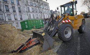 Des employés de la ville de Paris nettoient le fumier déposé par les manifestants devant le ministère de l'Agriculture, le 16 janvier 2013.