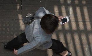 Une femme utilise son smartphone tout en marchant dans une rue