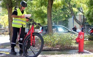 Un pompier de Rennes effectue une mission de vérification de poteau incendie avec un vélo électrique.
