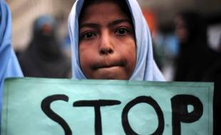 A Shiite student of Imamia Students Organization (ISO) holds a placard during a protest against an attack by Taliban militants at an army-run school in Peshawar the previous day, in Karachi on December 17, 2014.  Pakistan mourned 148 people - mostly children - killed by the Taliban in a school massacre that prompted global revulsion and put the government under new pressure to combat the scourge of militancy. Across the country many schools closed as a mark of respect, while others held special prayers for those killed in the bloodshed in the northwestern city of Peshawar. AFP PHOTO / Asif HASSAN