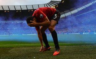 Rio Ferdinand, touché par une pièce de monnaie lors du derby entre Manchester United et Manchester City le 9 décembre 2012.