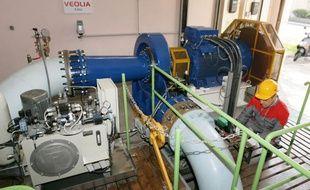 L'eau potable arrive par l'un des tuyaux bleu clair, entraîne la turbine bleu foncé, puis repart dans l'autre tuyau.