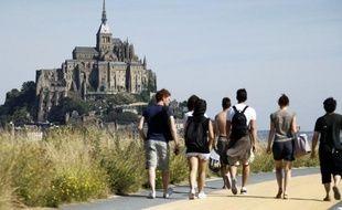 Trois mois après la fermeture des parkings qui défiguraient le mont Saint-Michel, au plus fort de l'été, les navettes reliant la côte au rocher fonctionnent mais nombre de touristes déplorent avoir tant à marcher, et en partie le long d'une zone commerciale.