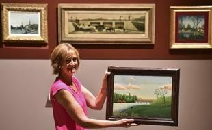 Antoinette Le Falher tenant le « Paysage avec pêcheur ».
