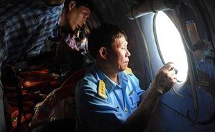 Un officier vietnamien effectue des repérages aériens pour trouver des traces du Boeing disparu de Malaysia Airlines le 9 mars 2014