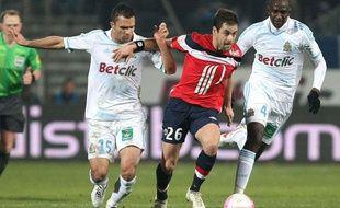 Le Lillois Joe Cole face aux Marseillais Morel et M'Bia, le 15 janvier 2012, au stade Vélodrome.