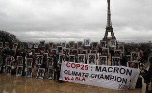 Une centaine de militants tiennent des portraits du président Emmanuel Macron pour exhorter la France à agir lors des négociations sur le climat de la COP 25 de l'ONU à Madrid, lors d'un rassemblement place du Trocadéro face à la Tour Eiffel à Paris, dimanche 8 décembre 2019.