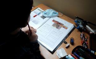 Ecolier travaillant a la maison lors du confinement et l arrêt des écoles lors de l'épidemie de Coronavirus, le 16 Mars 2020, Gace, France.