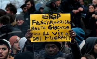 """En février 2018, un manifestant anti-raciste tient une pancarte avec le message suivant : """"Stop au fascisme et au racisme, arrêtez de jouer avec la vie des migrants""""."""