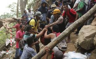 Les sauveteurs transportent une victime hors des décombres, après l'effondrement d'une mine d'or en Indonésie le 27 février 2019.