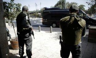 Deux policiers israéliens montent la garde à l'entrée d'un jardin public à l'ouest de Jérusalem, le 14 octobre 2015