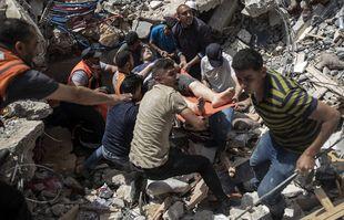 Un survivant sous les décombres d'un immeuble résidentiel détruit à la suite de frappes aériennes israéliennes dans la ville de Gaza, le 16 mai 2021.