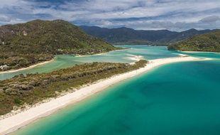 La plage Awaroa est une longue langue de sable blanc qui ferme une lagune turquoise surmontée de collines verdoyantes.