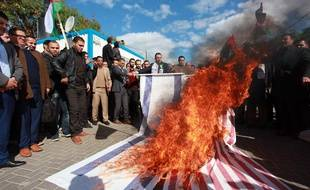 Des Palestiniens brûlent des drapeaux américains et israéliens le 7 décembre 2017 après la décision de Trump de reconnaître Jérusalem comme capitale de l'Etat d'Israël.