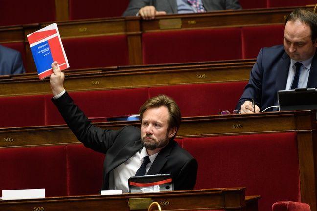 Le député socialiste Boris Vallaud brandit le règlement de l'Assemblée nationale.
