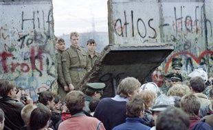 Des Allemands de l'Ouest regardent des gardes est-allemands ouvrir une brèche dans le Mur de Berlin,le 11 novembre 1989 près de la place Potsdamer