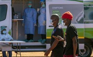 Des hommes devant une clinique de dépistage mobile du COVID-19 à  Johannesbourg, en Afrique du Sud, le mardi 21 avril 2020