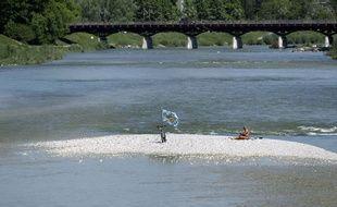 Un homme profite du soleil sur une ile au beau milieu de la rivière Isar dans les environs de Munich (Photo illustration).