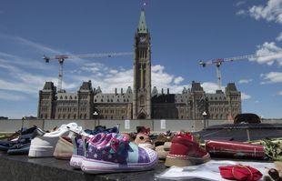 Des chaussures, des affiches et du tabac sont posés sur la flamme du centenaire en reconnaissance de la découverte de restes d'enfants sur le site d'un ancien pensionnat à Kamloops, en Colombie-Britannique, sur la colline du Parlement à Ottawa, en Ontario, le lundi 31 mai 2021.