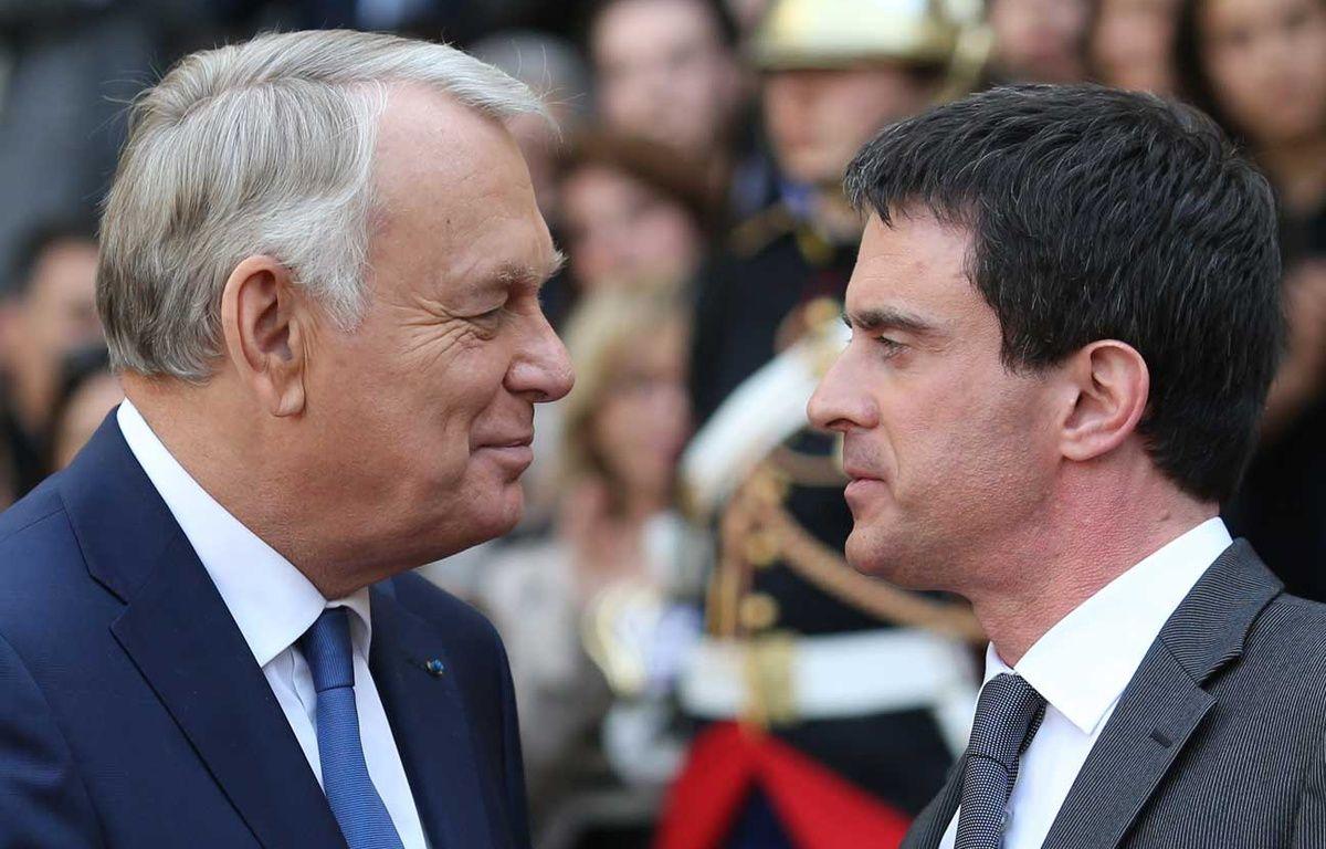 Manuel Valls et Jean-Marc Ayrault se serrent la main le 1er avril 2014. – KENZO TRIBOUILLARD / AFP