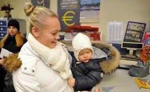 Une Lettone tient en main un sachet dans lequel se trouve des pièces de monnaie en euro, le 10 décembre 2013 à Riga